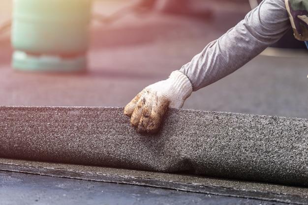 Asien-arbeiter, der teerfolie auf die dachspitze installiert