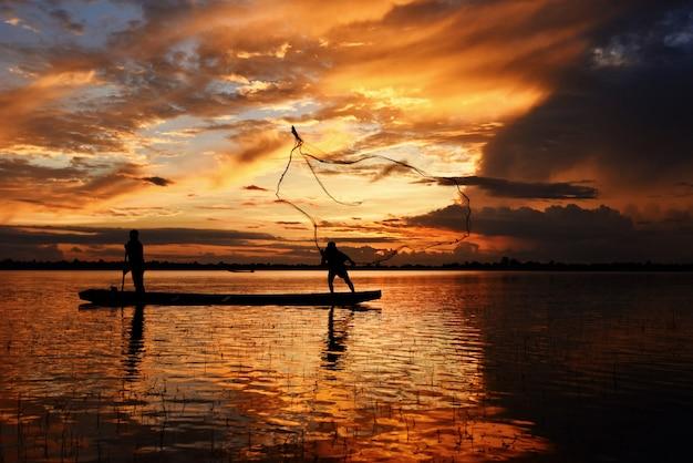 Asien-fischernetz unter verwendung auf hölzernem bootscasting-nettosonnenuntergang oder -sonnenaufgang im der mekong-schattenbildfischerboot.