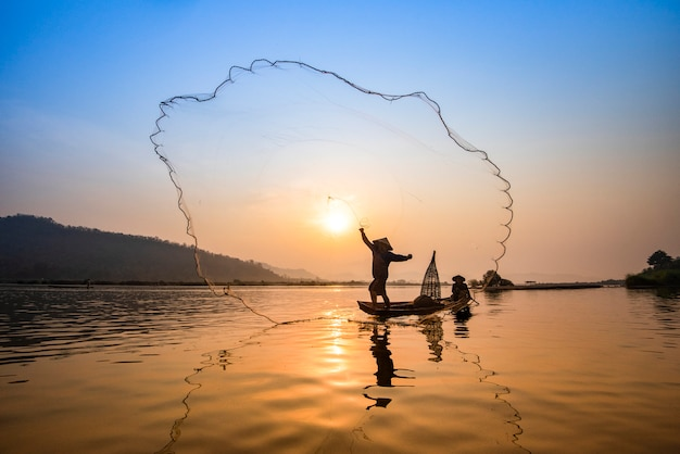 Asien-fischernetz unter verwendung des hölzernen boot casting-netzsonnenuntergangs oder -sonnenaufgangs im mekong