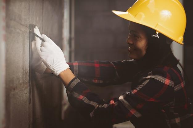 Asien-frau, der ingenieur, der an der standortarbeit arbeitet, mit glücklichem.