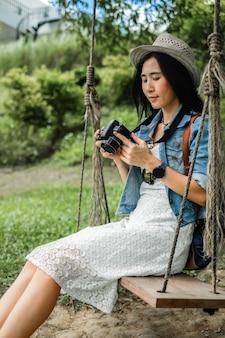 Asien-frau, die bild auf der kamera schaut.