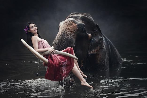 Asien-frau, die das trachtenmode-kostüm sitzt und aufwirft mit großem elefanten im fluss trägt