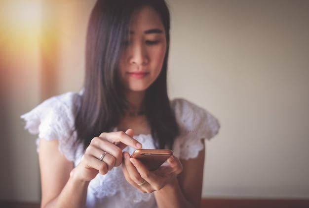 Asien-frau, die handy für das überprüfen von social media und von geschäftserfolg verwendet