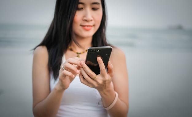 Asien-frau, die handy für die prüfung des social media verwendet