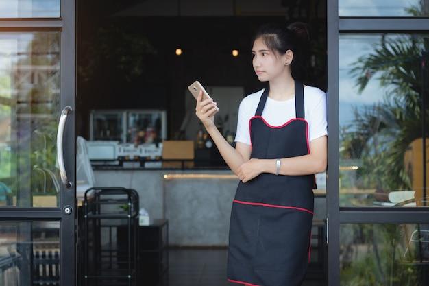 Asien-frau, die in der freizeit handy in der kaffeestube mit einsamem verwendet.