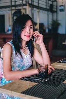 Asien-frau, die in der kaffeestube sitzt und handy verwendet.