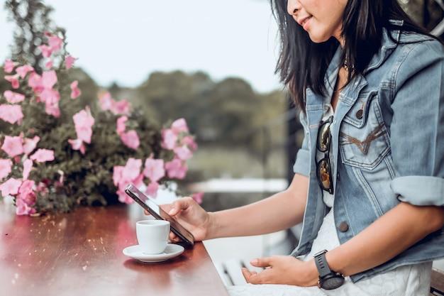Asien-frau, die in der kaffeestube sitzt und handy verwendet