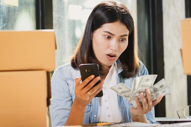 Asien-frau, die smartphone verwendet und geld mit überraschung betrachtet.