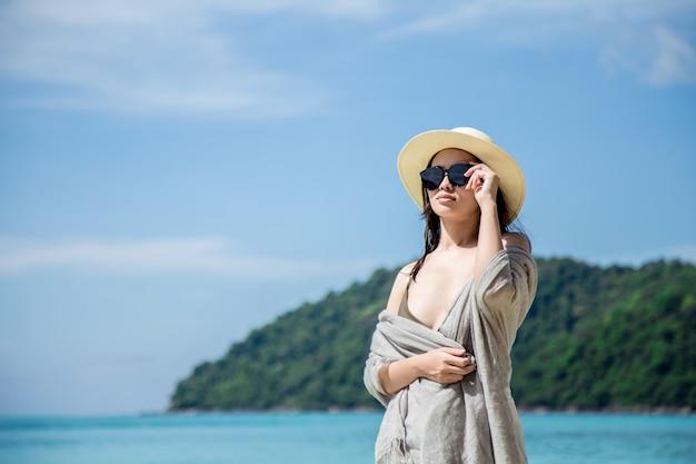 Asien-frau im bikini und in strohhut, die auf tropischem strand liegen