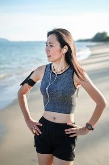 Asien-frau im sport trainieren und laufen auf dem strand.