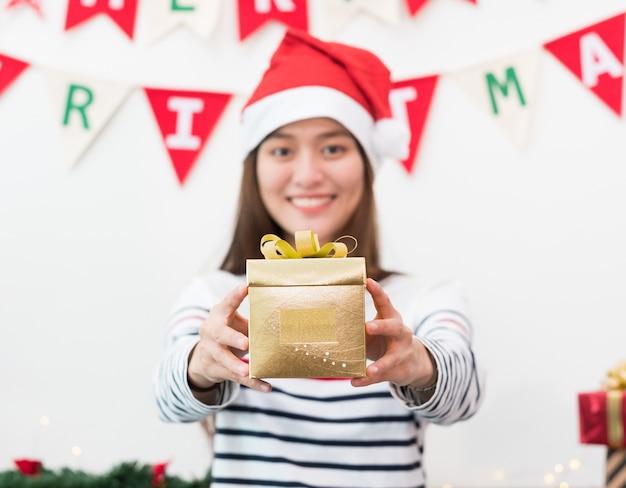 Asien-frau im weihnachtsfestgeschenk, das dem freund goldgold mit lächelndem gesicht in der weihnachtsfeier gibt