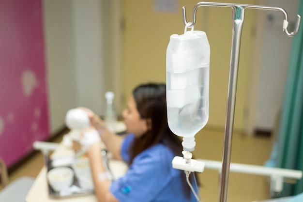 Asien-frau patien mit automatischer maschine der lösung der infusion iv im geduldigen raum