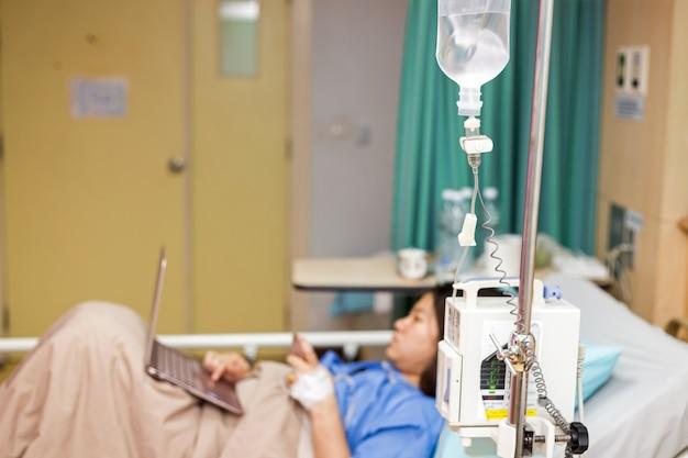 Asien-frauenpatient, der mit laptop während im krankenhaus arbeitet