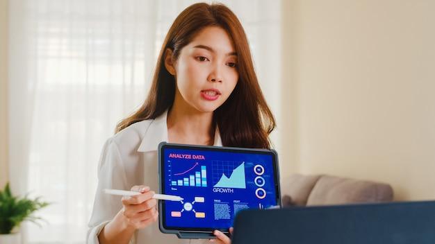 Asien-geschäftsfrau, die laptop- und tablet-präsentation zu kollegen über plan in videoanruf verwendet, während von zu hause im wohnzimmer arbeitend. selbstisolation, soziale distanzierung, quarantäne für coronavirus.