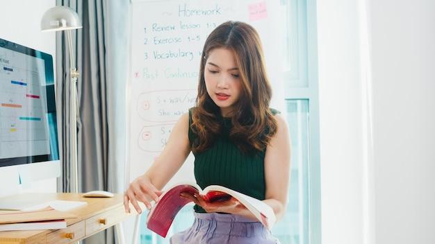 Asien junge weibliche englischlehrerin videokonferenz mit blick auf kamera sprechen von webcam lernen lehren im online-chat zu hause. fernunterricht, soziale distanzierung, quarantäne zur vorbeugung von koronaviren.