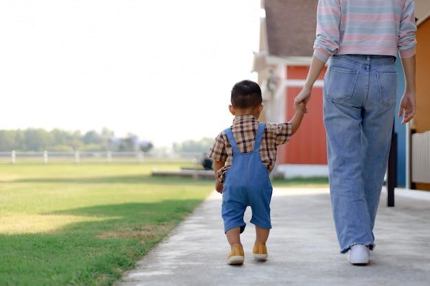 Asien-kleinkindjungenkind, das draußen spielt
