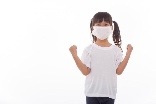 Asien-mädchen, das maske auf weißer wand trägt