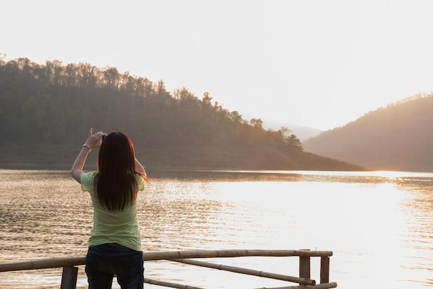 Asien-mädchen, das mobile verwendet, um aphoto bergblick zu nehmen
