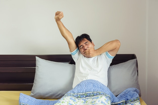 Asien-mann, der in bett nach aufwachen ausdehnt