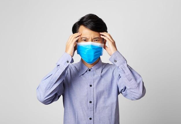 Asien-mann-panikstörung, die chirurgische maske trägt, die mund bedeckt
