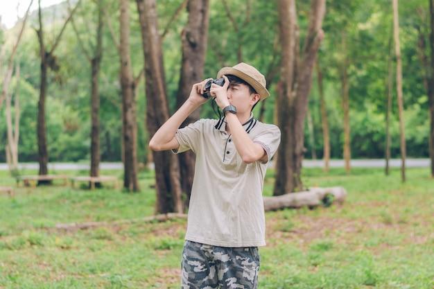 Asien-mann trägt hemd, hut und tarnungshose gehen und machen fotos am wald
