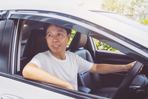 Asien-mannlächeln glücklich und antriebsauto