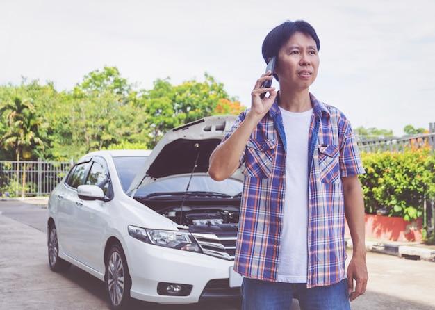 Asien-mannstandfrontseite ein defektes auto, das um unterstützung ruft