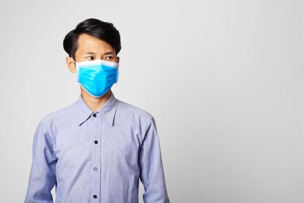 Asienmann, der chirurgische maske trägt, die mund und nase bedeckt
