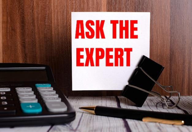 Ask the expert steht auf einer weißen karte auf einer holzoberfläche neben einem taschenrechner und einem stift