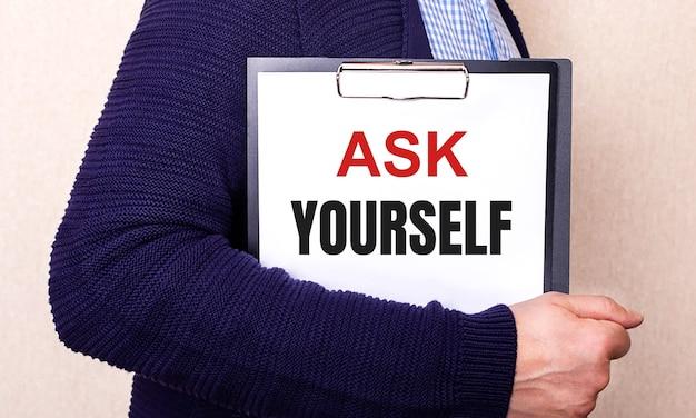 Ask yourself steht auf einem weißen blatt, das von einem seitlich stehenden mann gehalten wird