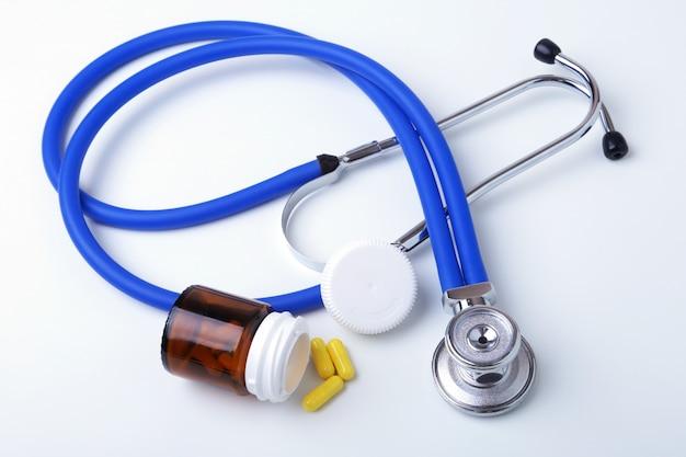 Asorted pilse und ein stethoskop auf weißem hintergrund