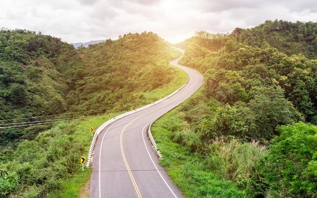 Asphalt gebogene landstraße auf gebirgshintergrund