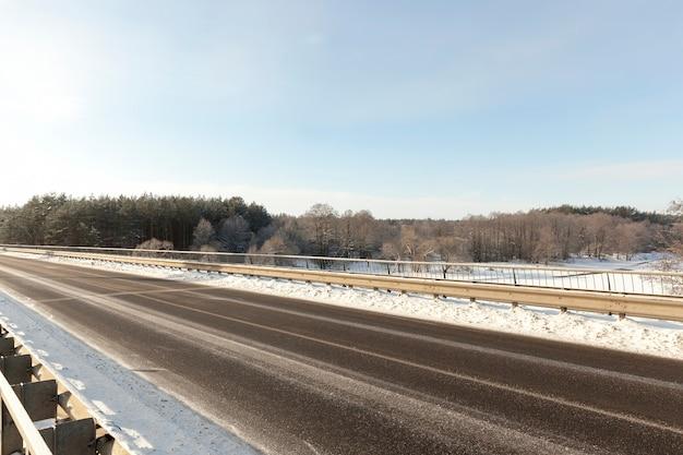 Asphaltierte straße im winter mit schnee bedeckt