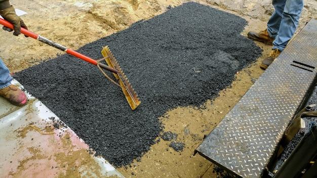 Asphaltierungsfertigermaschine der arbeitskraft während der straßenstraße, die arbeiten repariert