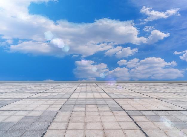 Asphaltpflaster und quadratische bodenfliesen unter dem blauen himmel und den weißen wolken