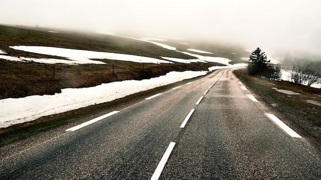 Asphaltstraße auf einem mit schnee im winter bedeckten hügel