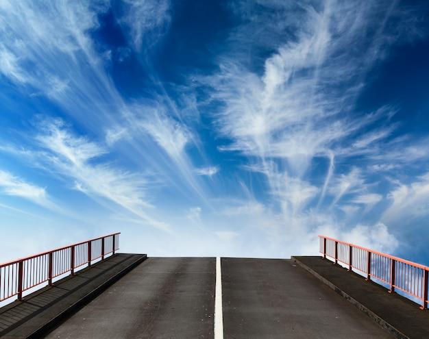 Asphaltstraße, die mit wolken in den himmel geht
