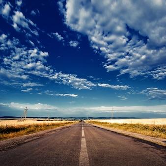 Asphaltstraße durch das gelbe feld und wolken am blauen himmel im herbsttag
