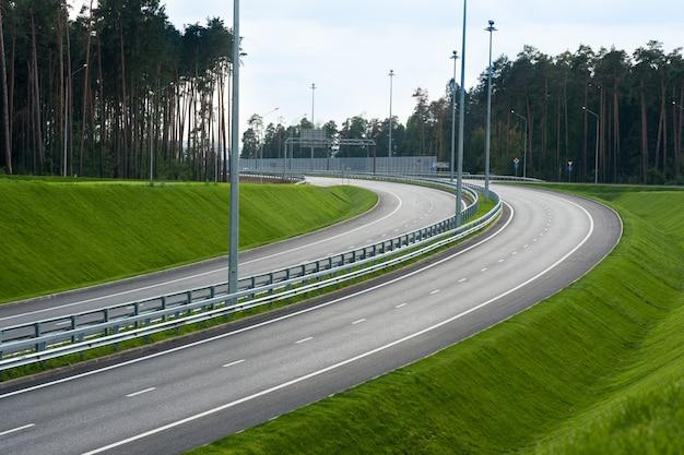 Asphaltstraße durch das grüne feld und die wolken auf blauem himmel am sommertag