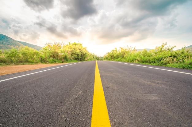 Asphaltstraße durch das grüne feld und wolken auf blauem himmel am sommertag