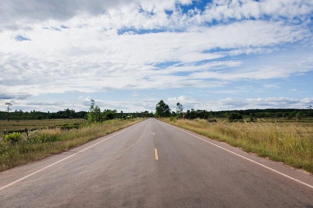 Asphaltstraße durch das reisfeld und wolken am blauen himmel