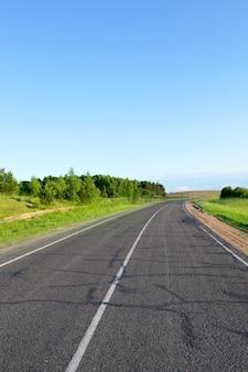 Asphaltstraße im sommer, landschaft mit grünem gras und blauem himmel