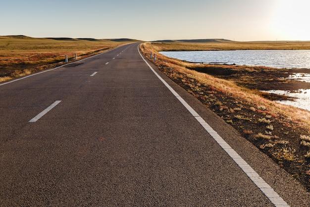 Asphaltstraße in der mongolischen steppe entlang einem kleinen see