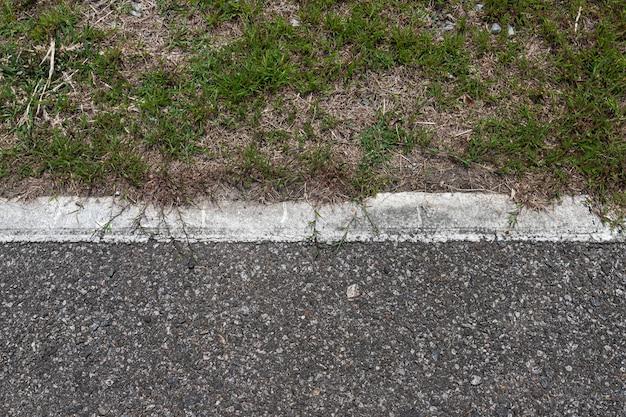 Asphaltstraße mit streifen und beschaffenheit hintergrund des grünen grases, leerer kopienraum.