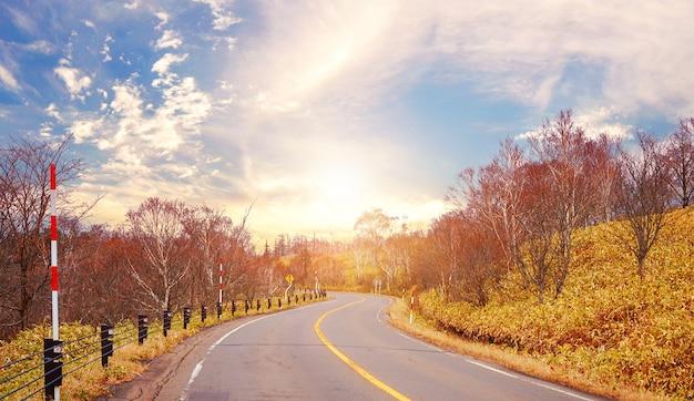 Asphaltstraße und berge bei schönem sonnenuntergang