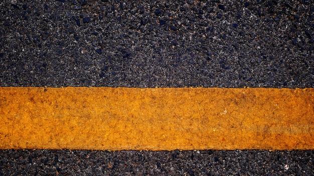 Asphaltstraße und gelbe linie in einer dunklen nacht, hintergrundasphalt
