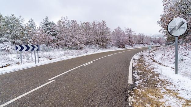 Asphaltstraße zum schneebedeckten berg mit verkehrszeichen erlaubt überholen. madrid.