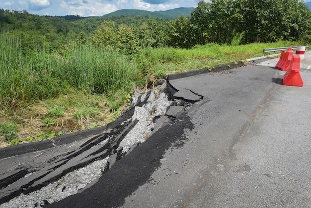 Asphaltstraße zusammengebrochen und risse am straßenrand - erdrutsch mit kunststoffsperren auf bergauf