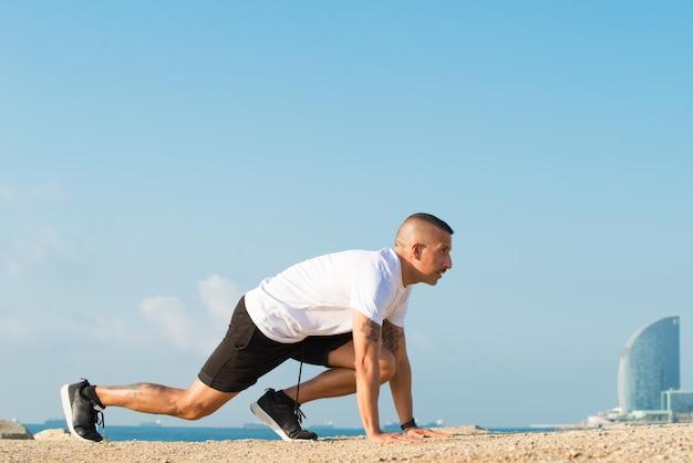 Aspirierter läufer in ausgangsposition am strand