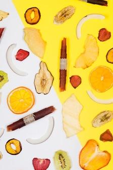 Asprtied getrocknete früchte, chips verstreut auf weißem und gelbem hintergrund. fruchtchips. gesundes ernährungskonzept, snack, kein zucker. ansicht von oben, kopienraum.